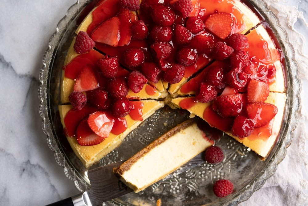 Overhead shot of a Keto Cheesecake topped with fresh berries and strawberry jelly