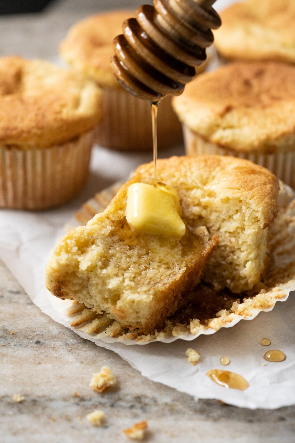 Drizzling keto maple syrup onto a halved low carb cornbread muffin