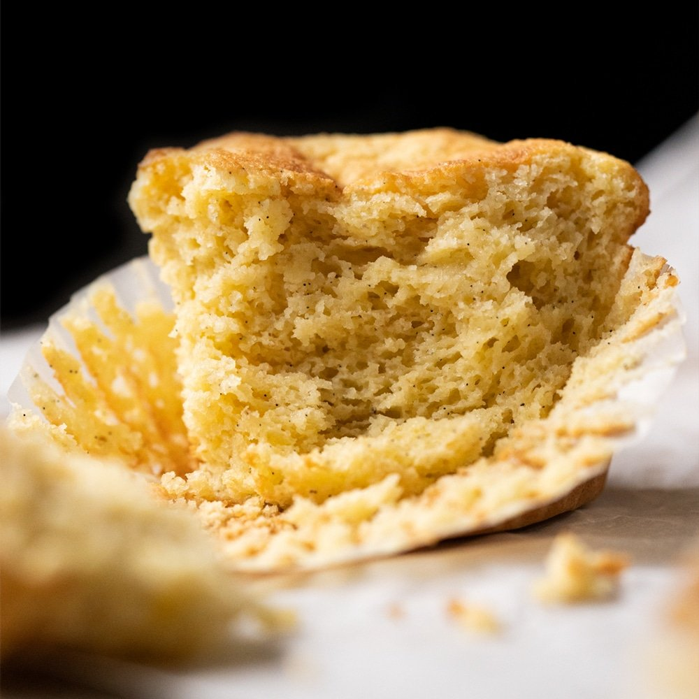 A pinched keto cornbread muffin showing the tender crumb
