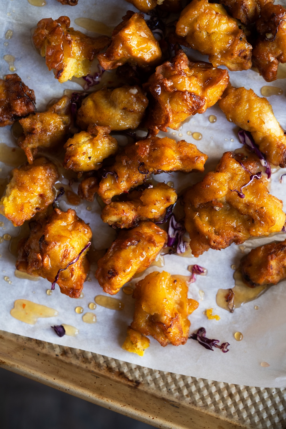 Mixing the fried battered chicken bites with the orange glaze on a baking tray