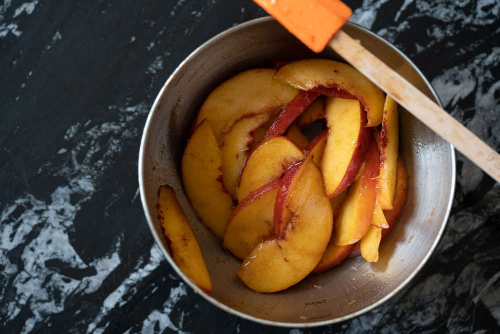 Sliced peaches macerating in a metal bowl over a black marble surface with a spatula on the side