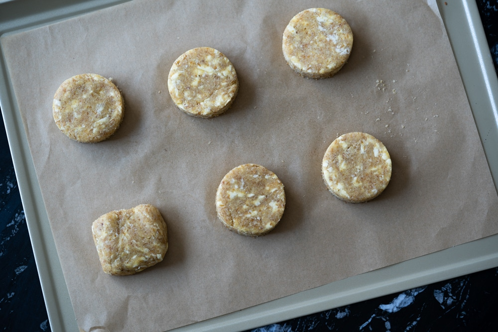 Overhead shot of six unbaked keto shortcakes on a baking tray with parchment paper